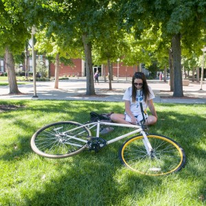 Student on lawn with bicycle.