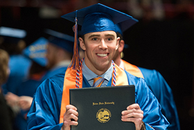 Image of a college graduate holding his diploma.