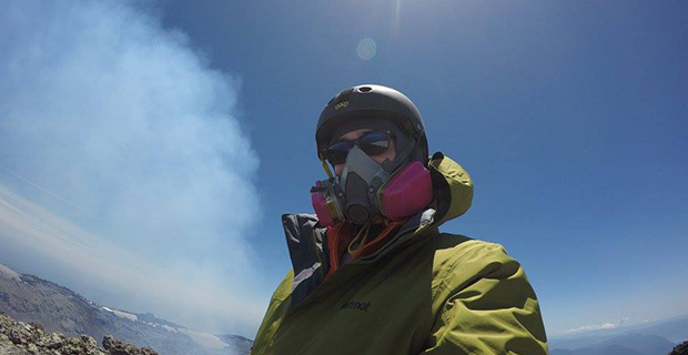 Researcher in helmet and gas mask by volcano in Chile