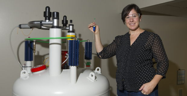 Image of Lisa Warner next to lab equipment