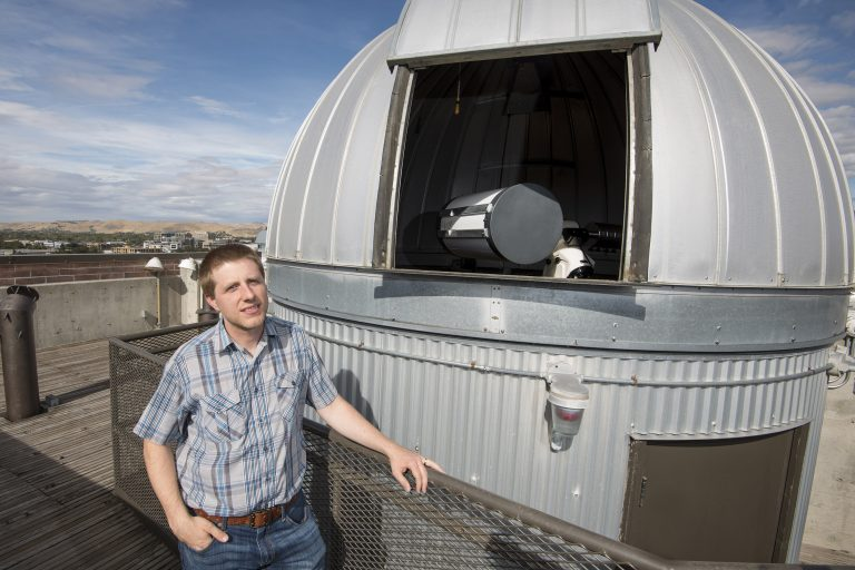 Brian Jackson stands next to telescope