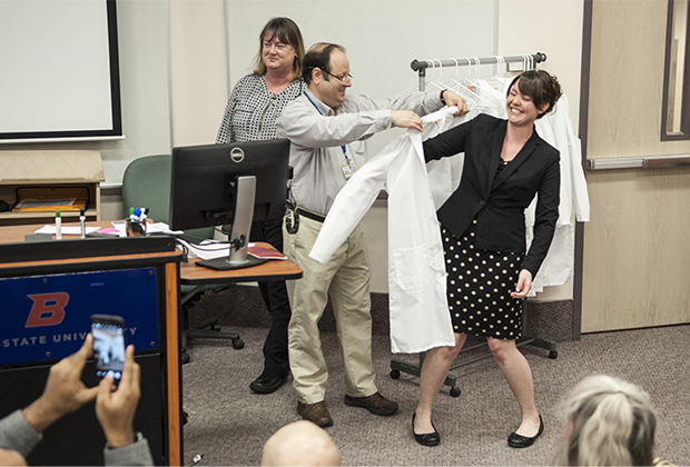 studentaccepting white coat from faculty