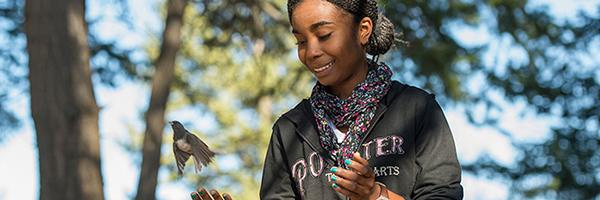 student releasing a bird